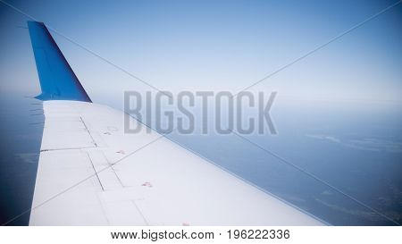 Wing of an airplane against the background of the merging sky with the earth
