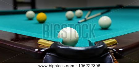 Billiard balls and two cue sticks on green game table
