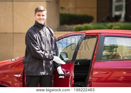 Portrait Of A Happy Young Male Valet Opening Red Car Door
