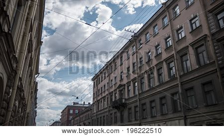 St. Petersburg houses connected by a web of high-voltage wires against a cloudy sky background