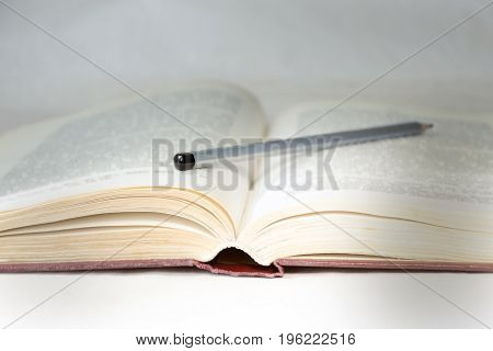 The Light Of Knowledge Is An Open Book Close-up, Illuminated By A Ray Of Light, With A Pencil On It.