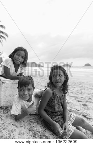 EL NIDO PALAWAN PHILIPPINES - JANUARY 20 2017: Black and white picture of filipino trio posing to the camera at Nacpan Beach Philippines.