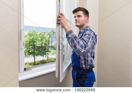 Young Male Handyman In Uniform Installing Window