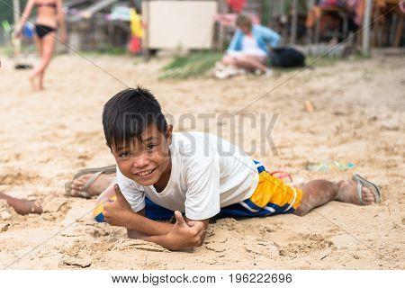 EL NIDO PALAWAN PHILIPPINES - JANUARY 20 2017: Local filipino boy lying down on the sand while pose to the camera at Nacpan Beach.