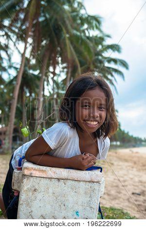 EL NIDO PALAWAN PHILIPPINES - JANUARY 20 2017: Filipino girl smiling while leaning against a styrofoam box at Nacpan Beach Philippines.