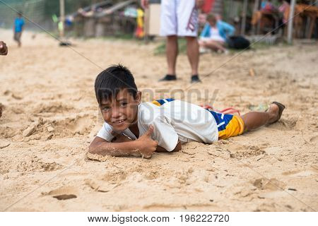 EL NIDO PALAWAN PHILIPPINES - JANUARY 20 2017: Local filipino boy lying down on the sand while pose to the camera at Nacpan Beach Philippines.