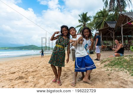 EL NIDO PALAWAN PHILIPPINES - JANUARY 20 2017: Wide angle picture of filipino trio posing to the camera at Nacpan Beach Philippines.