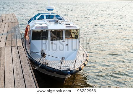 A modern motor boat near the old wooden pier on the lake in the evening