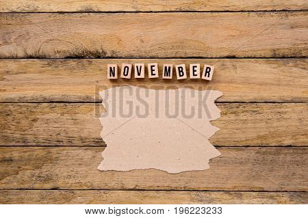 November - Calendar Month In Wooden Block Letters With Handmade Paper For Copy Space On Wooden Backg