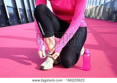 Young woman age 30 tying her shoelaces on a bright pink cycleway road in Auckland New Zealand. Real people. Copy space.