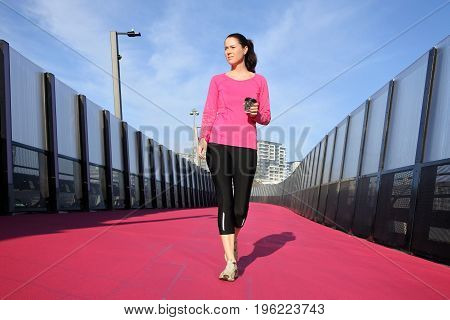 Young Woman Walking On A Bright Pink Road