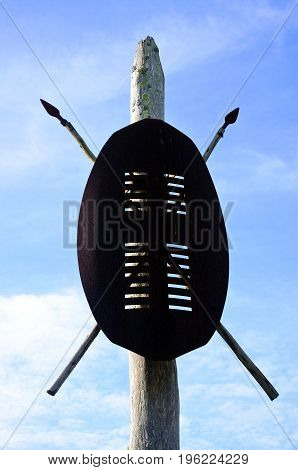 African tribal war shields and spears on a wooden pole against blue sky in Africa.