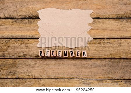 December - Calendar Month In Wooden Block Letters With Handmade Paper For Copy Space On Wooden Backg