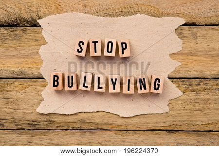 Stop Bullying - in wooden letters on torn handmade paper on rustic wooden background