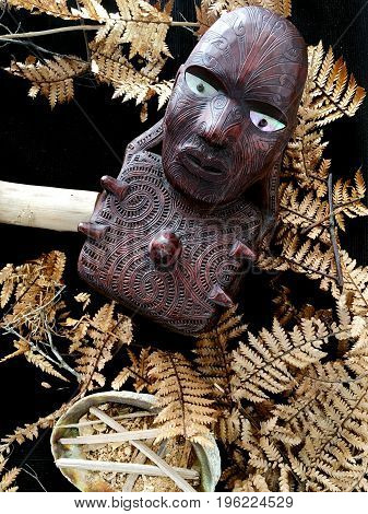 Maori wooden carving artwork on a background texture over New Zealand fern leaves.