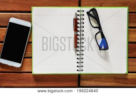 Smartphone Book with pencil and glasses on wood table background