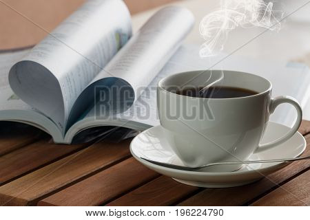 Coffee cup hot with book on a wooden table