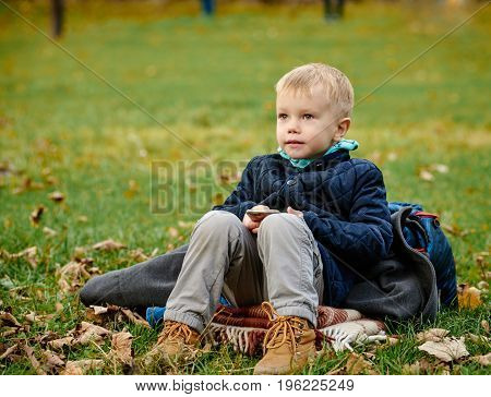 Portrait of smiling child sitting outdoors in autumn park
