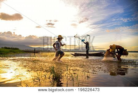 Asian boy and girl playing in the river with fisherman in the morning sunrise Thailand