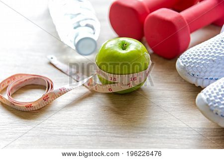 Healthy lifestyle sport equipment fitness sneakers green apple fresh water and healthy food on blue wood background. Healthy Concept.