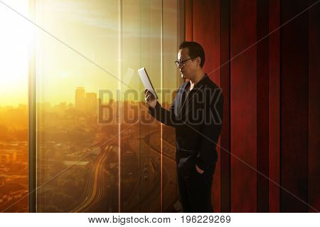 Young asian businessman holding and using digital tablet . Sunrise scene .