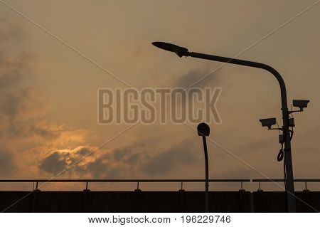 Silhouette LED Light poles and cctv on an Expressway with orange cloudy sky background ;Bangkok thailand.
