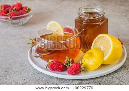 Prevention and treatment of influenza and colds. Ripe raspberries, fresh lemon, a glass jar with honey and a mug with hot tea on a white round tray on a light background.  Used in folk medicine.