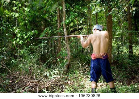 Asian Man Farmer Aiming Gun A Rifle Walks Along In The Forest Background. Hunting And The Way Of Lif