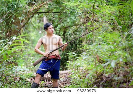 Asian Man Farmer Carrying A Rifle Walks Along In The Forest Background. Hunting And The Way Of Life