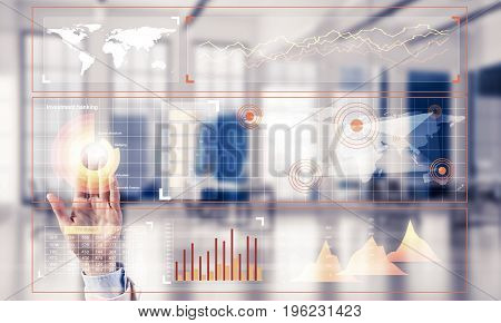 Hand of businesswoman working with media interface on screen and office interior at background