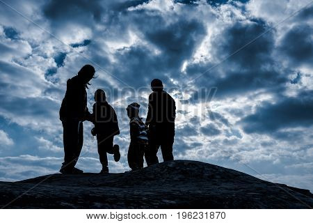 Silhouette back view of happy and friendly family. Father and mother with children hikers enjoying view at the top of a mountain against blue sky with dark cloudy in a winter's day. Travel on vacation