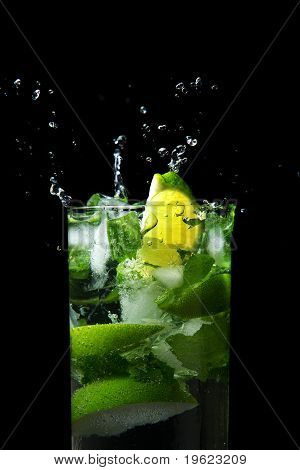 Wedge of lime falling into a drink