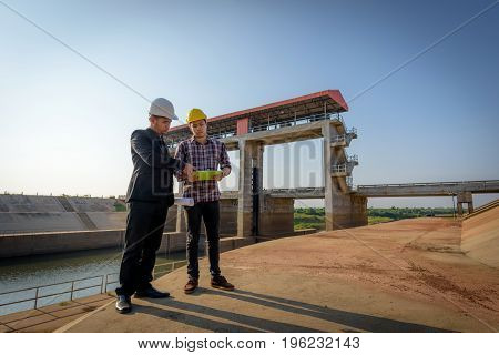 Business Men Meeting With Engineers And Foremen Are Standing Reading Reports On Construction Sites.