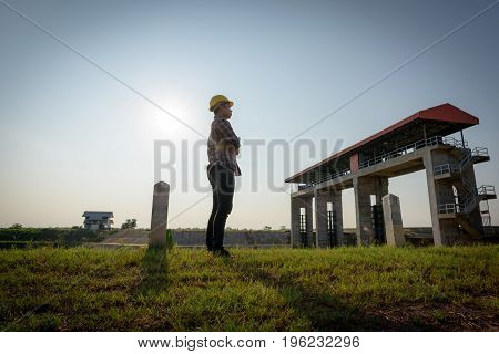 Male Employee Holds Standing While Looking At A Public Floodgate.