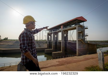 Close Up. Male Employee Standing While Pointing To A Public Floodgate.