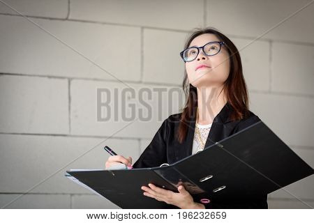 Businesswoman Is Writing A Report In A Brick Building.