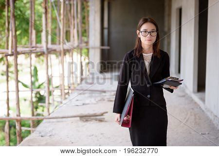 Businesswoman Standing Holding A File And A Calculator.