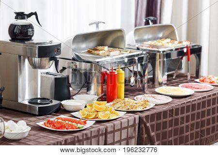 Breakfast at the hotel. Buffet Table with dishware waiting for guests. hot meals, vegetables, fruits, meats, cheeses. Coffee machine. Selective focus