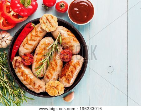 Top view of chicken homemade sausages, sauces ketchup and vegetables and herbs on blue wooden background. Grilled sausages and grilled vegetables in black iron pan. Copy space. Top view or flat lay.