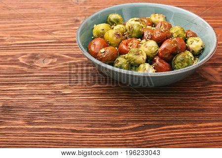 Oven baked brussels sprouts and tomatoes with pistachios. Low fat healthy eating concept.