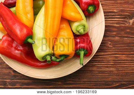 Fresh colored sweet peppers on the plate on wooden background table