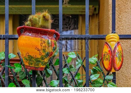 Traditional handmade and painted provencal pottery in the shape of a bee and a pot for a plant decorating a window in the old town of Menton on the French Riviera or Cote d'Azur