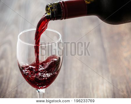 Closeup of red wine pouring in glass. Copy space. Sunflare effect