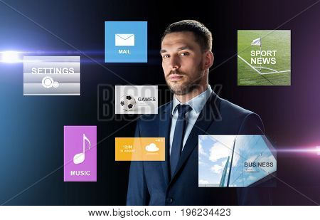 business, people and technology concept - businessman in suit over black background with virtual applications