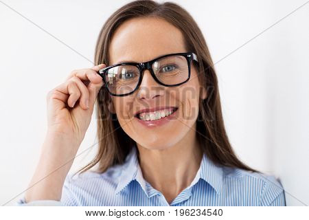 people, business and vision concept - close up of happy smiling middle aged woman in glasses