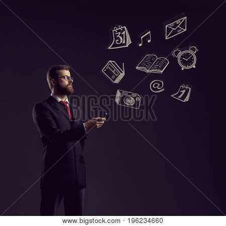 Businessman checking his smartphone over dark dramatic background. Business, office, idea concept.