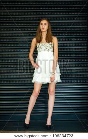 Fashion portrait of pretty sexy young brunette woman in white dress posing on dark wall background