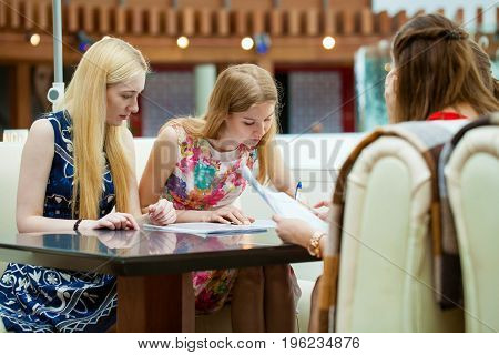 Beautiful young women or lawyers, discussing and signing a contract or legal document