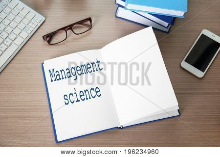 Open notebook with text MANAGEMENT SCIENCE on wooden table