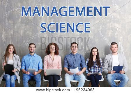 Concept of management science. Young people sitting on chairs against grunge wall background